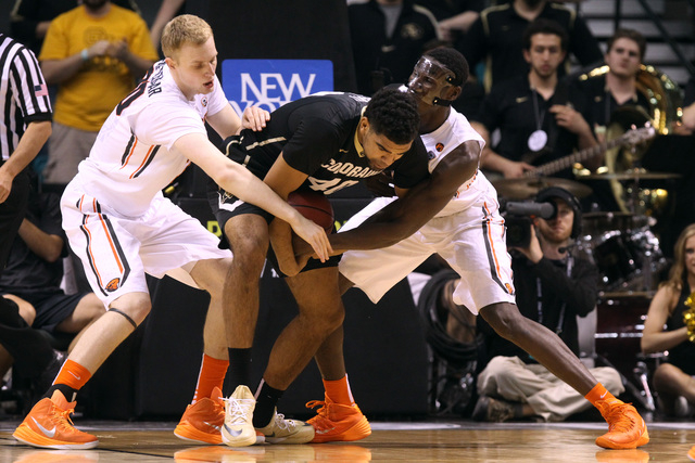 Colorado forward Josh Scott tries to keep the ball away from Oregon State forwards Olaf Schaftenaar, left, and Daniel Gomis during the second half of their Pac-12 Conference tournament game Wednes ...
