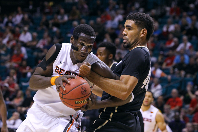 Colorado forward Josh Scott defends Oregon State forward Daniel Gomis during the second half of their Pac-12 Conference tournament game Wednesday, March 11, 2015, at the MGM Grand Garden Arena. Co ...