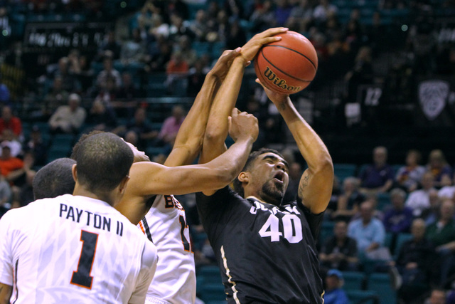 Colorado forward Josh Scott is fouled by Oregon State guard Malcolm Duvivier during the second half of their Pac-12 Conference tournament game Wednesday, March 11, 2015, at the MGM Grand Garden Ar ...