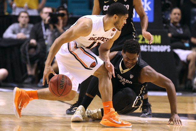 Colorado forward Tory Miller hits the floor after taking a shot in the midsection from Oregon State guard Malcolm Duvivier during the first half of their Pac-12 Conference tournament game Wednesda ...