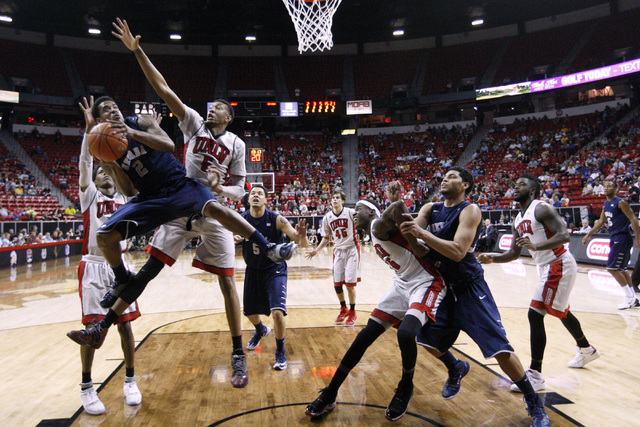 UNR guard Tyron Criswell is guarded by UNLV forward Chris Wood while trying to shoot during the first half of their Mountain West Conference tournament game Wednesday, March 11, 2015, at the Thoma ...