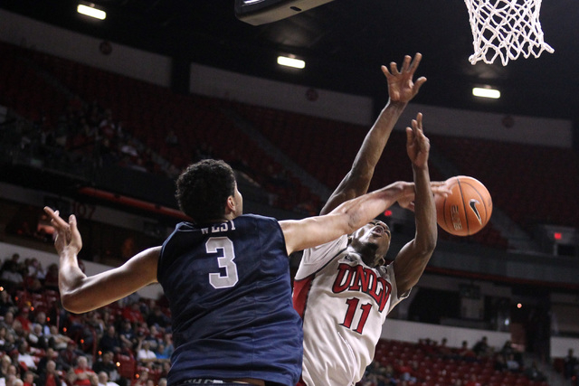 UNR forward A.J. West blocks a shot by UNLV forward Goodluck Okonoboh during the second half of their Mountain West Conference tournament game Wednesday, March 11, 2015, at the Thomas & Mack Cente ...
