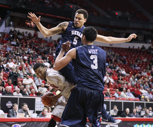 UNR forward Kaileb Rodriguez lands on top of UNLV forward Chris Wood while trying to defend him during the second half of their Mountain West Conference tournament game Wednesday, March 11, 2015,  ...