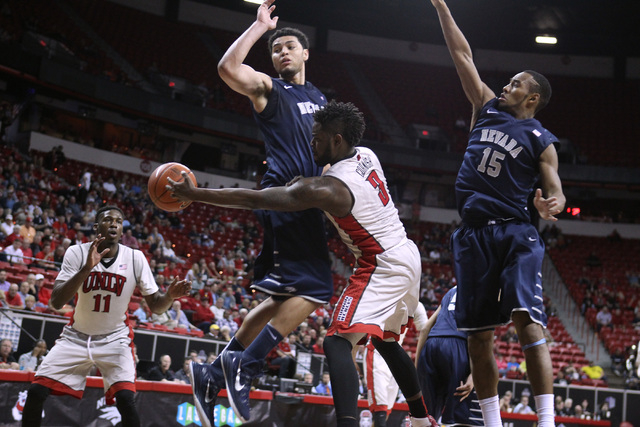 UNLV guard Jordan Cornish passes around UNR forward A.J. West to UNLV forward Goodluck Okonoboh during the second half of their Mountain West Conference tournament game Wednesday, March 11, 2015,  ...