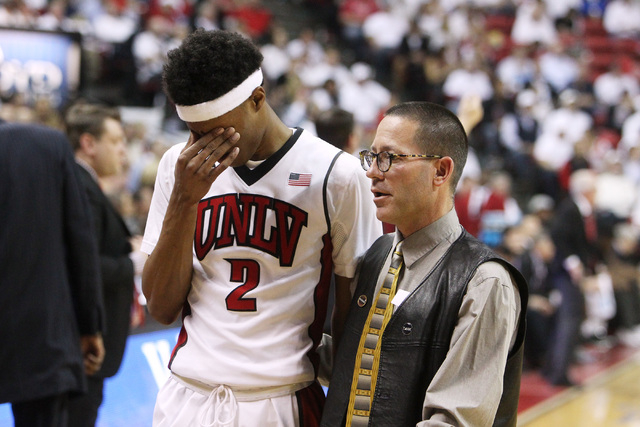 Trainer Dave Tomchek walks UNLV guard Patrick McCaw off the court after McCaw suffered a head injury during the second half of their Mountain West Conference game Wednesday, March 4, 2015, at the  ...
