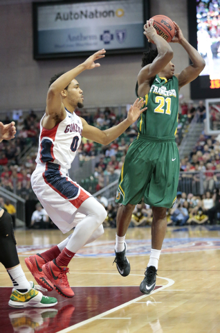 San Francisco Dons guard Devin Watson prepares to pass across court to a teammate while being defended by Gonzaga University guard Silas Melson (0) during the Western Athletic Conference Champions ...