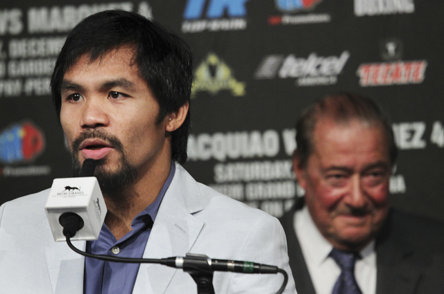 Boxer Manny Pacquiao speaks during a press conference at the MGM Grand hotel-casino in Las Vegas, Dec. 5, 2012 as fight promoter Bob Arum looks on. Pacquiao is scheduled to take on rival Juan Manu ...