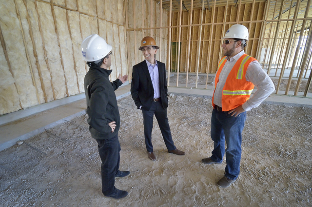 John Woo, vice president of asset management for Equity Office, center, talks with Cesar Shih, left, and Chris Chebegia on the construction site of a 12,000-square-foot retail center in the  Hughe ...
