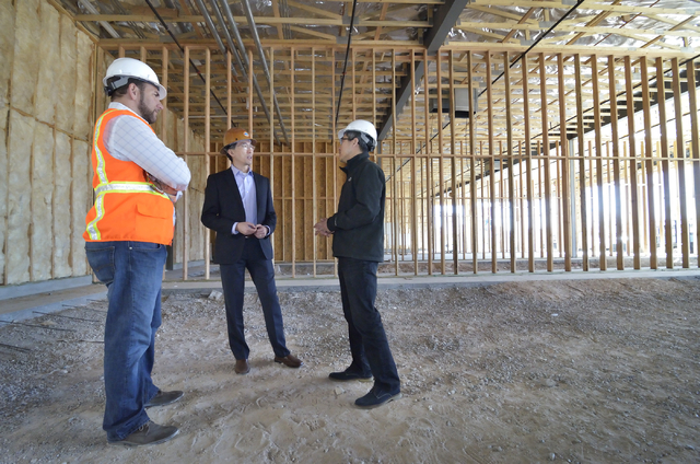 John Woo, vice president of asset management for Equity Office, center, talks with Chris Chebegia, left, and Cesar Shih on the construction site of a 12,000-square-foot retail center in the  Hughe ...