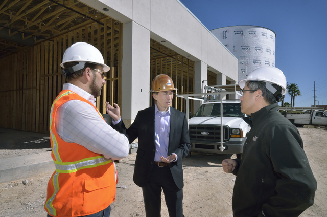 John Woo, vice president of asset management for Equity Office, center, talks with Chris Chebegia, left, and Cesar Shih on the construction site of a 12,000-square-foot retail center on the northw ...