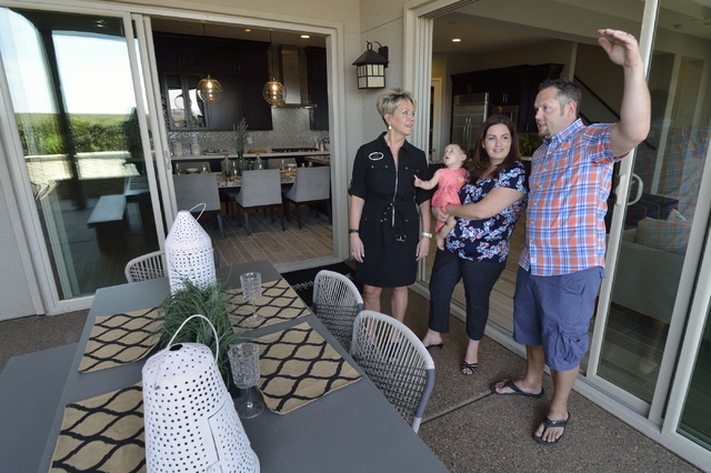 Trish Nash, broker/owner with Signature Gallery of Homes, left, looks at a Woodside Homes model home with, from left, Maci, Jodi and Eric Gilliland at the Cadence masterplanned community in Hender ...