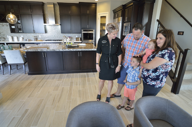 Trish Nash, broker/owner with Signature Gallery of Homes, left, looks at a Woodside Homes model home with Eric and Jodi Gilliland and their children Tyler, standing, and Maci at  the Cadence maste ...