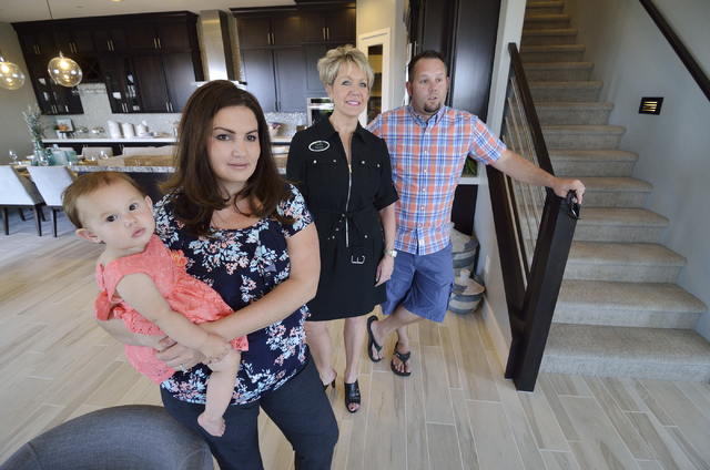 Trish Nash, broker/owner with Signature Gallery of Homes, second from right, looks at a Woodside Homes model home with, from left, Maci, Jodi and Eric Gilliland at the Cadence masterplanned commun ...