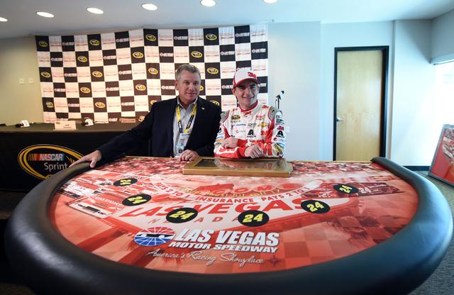 Las Vegas Motor Speedway president Chris Powell, left, presents NASCAR Sprint Cup Series driver Jeff Gordon a commemorative poker table to celebrate his retirement tour during Stratosphere Pole Da ...