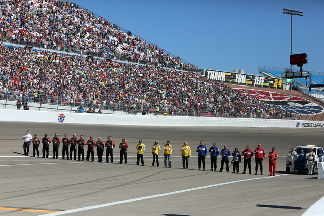 Track workers stand during the National Anthem before the start of the NASCAR Sprint Cup Series Kobalt 400 race at the Las Vegas Motor Speedway on Sunday, March 8, 2015. (Bizuayehu Tesfaye/Las Veg ...