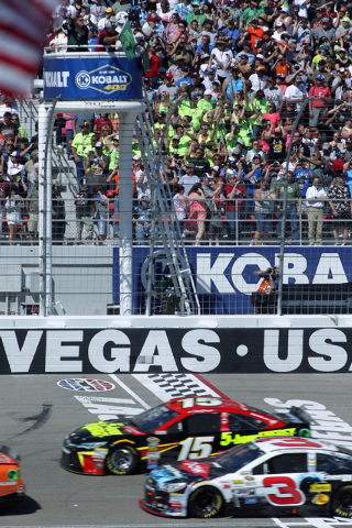 The green flags waves to start the NASCAR Sprint Cup Series Kobalt 400 race at the Las Vegas Motor Speedway on Sunday, March 8, 2015. Pictured crossing the start/finish line are Clint Bowyer (15)  ...