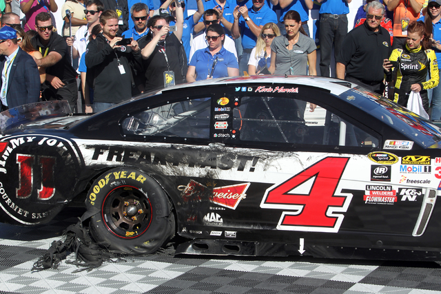 Kevin Harvick pulls into Victory Lane with a thrashed tire from a burnout celebration after winning the NASCAR Sprint Cup Series Kobalt 400 race at the Las Vegas Motor Speedway on Sunday, March 8, ...