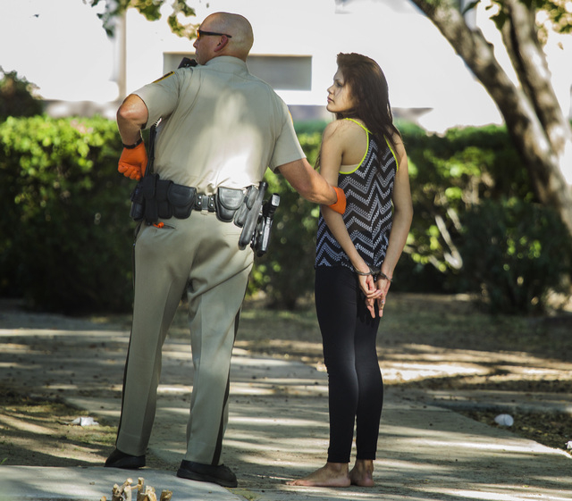 Las Vegas police officer leads an alleged suspect at Kendale Street near Karen Avenue involve in a hit and run on Monday, March 30,2015. Two people were detained in the accident that injured three ...