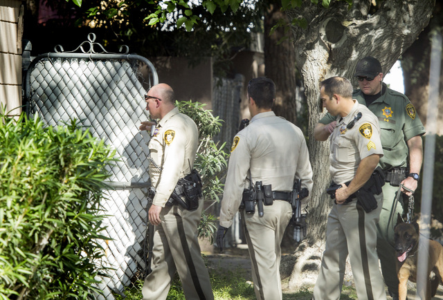 Las Vegas police officers enter an apartment searching for  for hit and run suspects on Kendale Street near Karen Avenue on Monday, March 30,2015. Two people were detained in the accident that inj ...
