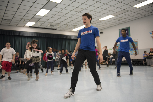"Newsies cast members, from center in blue shirts, Chaz Wolcott and Jordan Samuels teach kids a dance routine as part of Disney Theatrical Productions' new wellness and fitness program ""Get Up ..."