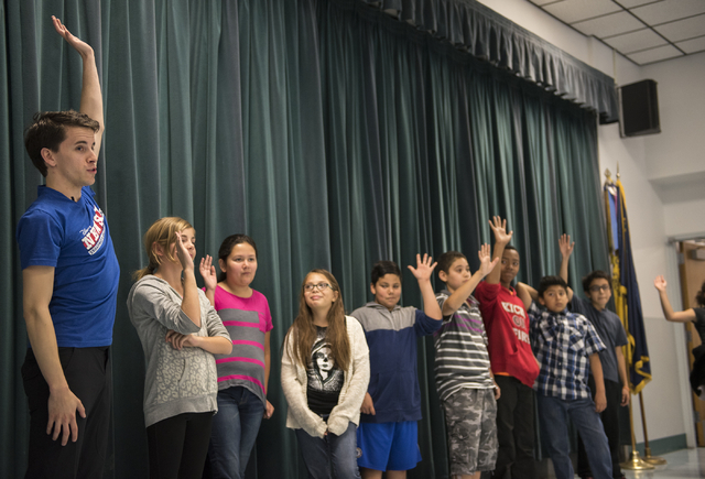 "Newsies cast member Chaz Wolcott, left, interacts with kids as part of Disney Theatrical Productions' new wellness and fitness program ""Get Up and Go"" at Doris French Elementary School i ..."