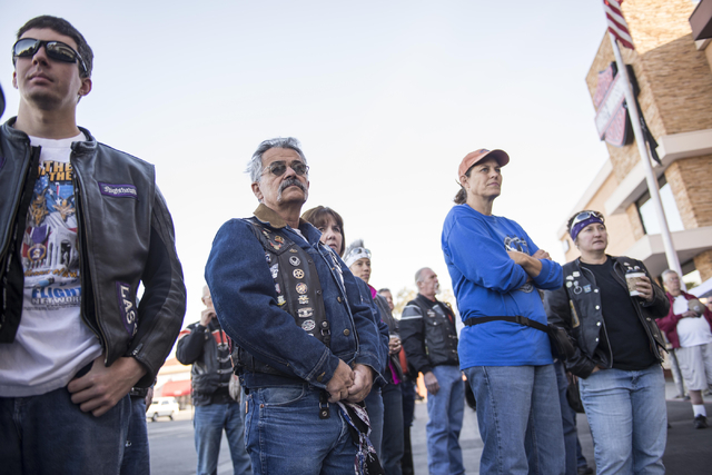 Attendees watch the Las Vegas Metropolitan Police Department honor guard during the annual Scoot and Shoot Poker Run on Saturday, March 21, 2015, at Red Rock Harley-Davidson in Las Vegas. The even ...