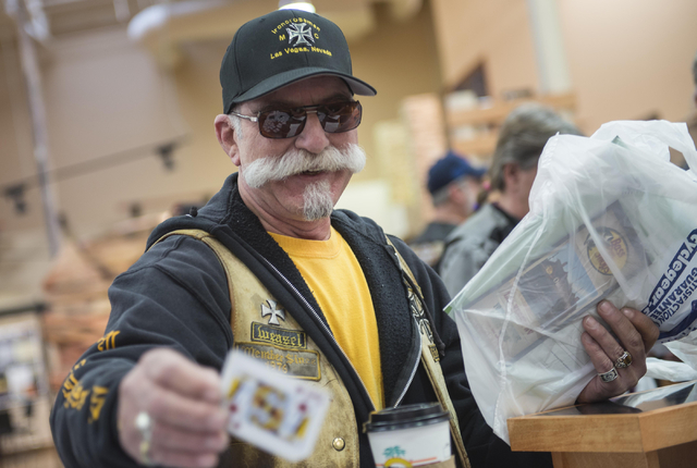 Frank Tegano pulls a playing card during the annual Scoot and Shoot Poker Run sponsored by the Las Vegas Metropolitan Police Department on Saturday, March 21, 2015, at Red Rock Harley-Davidson in  ...