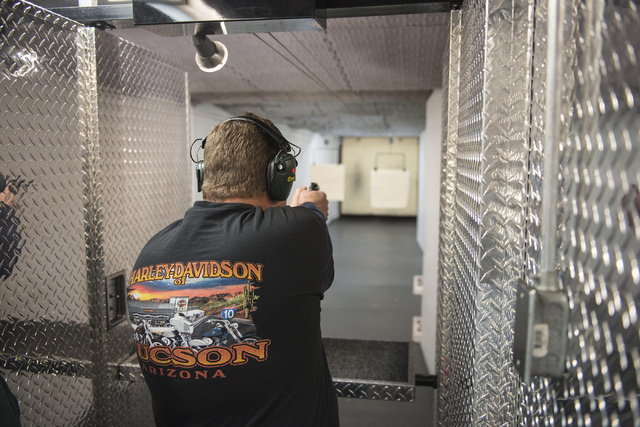 Jeffrey Bengel shoots at a playing card target at Bass Pro Shops in the Silverton casino in Las Vegas during the annual Scoot and Shoot Poker Run on Saturday, March 21, 2015. The event, sponsored  ...