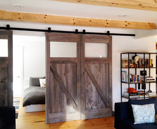 Courtesy Real Carriage Door Co. Rustic doors adorn this a guest bedroom off the main living room area.