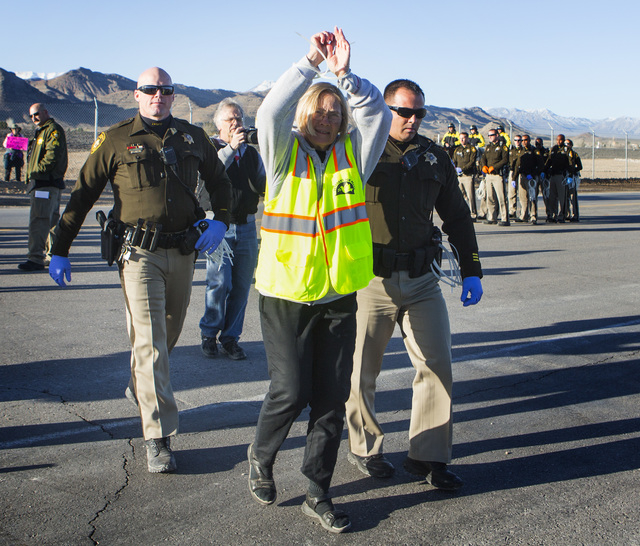 Former U.S. Army colonel and retired State Department official Ann Wright raises her hands after being arrested by Las Vegas police during an anti-drone warfare protester at the south entrance to  ...