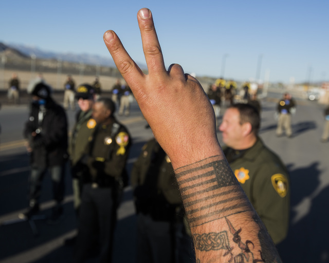 Former serviceman Jason Maluhia raises a peace sign shortly before he is arrested by Las Vegas police at the south entrance to Creech Air Force Base at Indian Springs on Friday, March 6, 2015. Thi ...