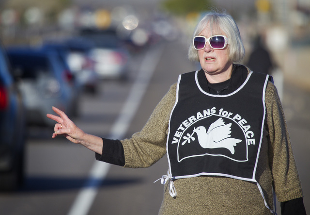 Anti-drone protester S. Jenika flashes a peace sign while traffic is backed up on U.S. 95 near Creech Air Force Base in Indian Springs on Friday, March 6, 2015. Thirty-three protesters were cited  ...