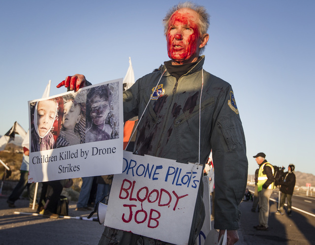Anit-drone protester Dennis DuValle wears theatrical paint while standing near the  south entrance to Creech Air Force Base at Indian Springs on Friday, March 6, 2015. Nearly 150 anti-drone warfar ...