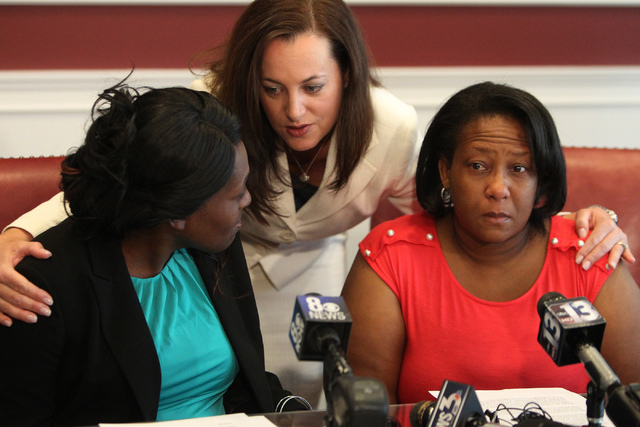 Nychele Thomas, left, and Angela Gilmore, right, mothers of two teenagers who died in a crash with drunk driver on March 5, are comforted by one of their attorneys, Heather Harris, following a pre ...