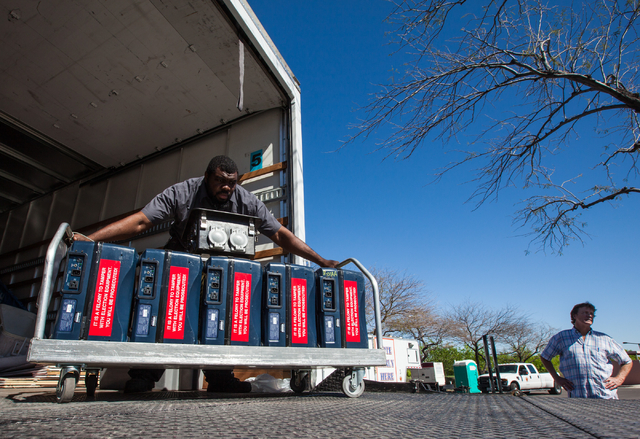 Clark County employee Chad Carter moves a set of voting machines out of a truck while setting up a mobile trailer for early voting for the Las Vegas municipal elections at Trails Village Center, 1 ...
