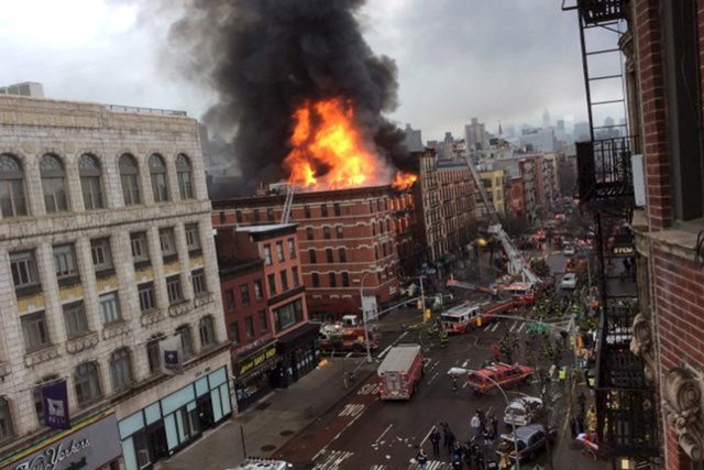 Fire shoots from the roof of a building after it collapsed and burst into flames in New York City's East Village as seen in this picture taken by Scott Westerfeld March 26, 2015. (REUTERS/Scott We ...