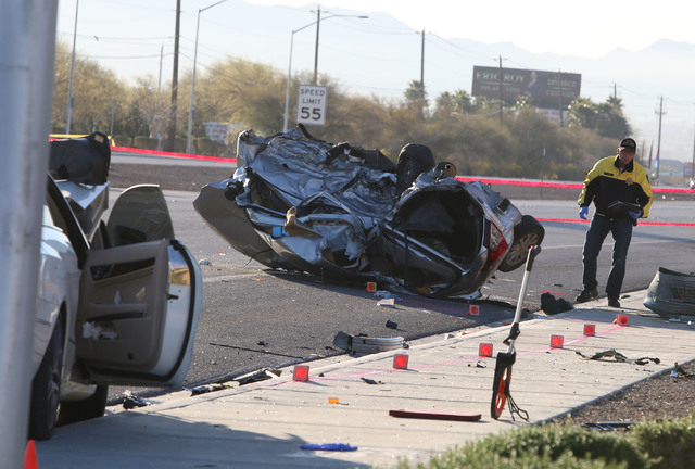 A Metro police officer investigates the crash at Boulder Highway and Russell Road where two women were killed Thursday, March 5, 2015. (Bizuayehu Tesfaye/Las Vegas Review-Journal)