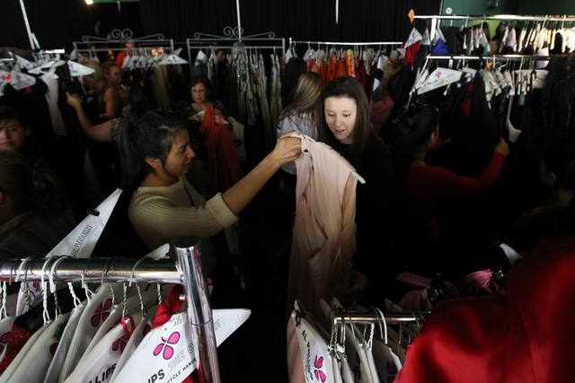 Sandra Kassandra Delgado shows a dress to Rachel Reimschussel at the annual Gown Town event, sponsored by HELP of Southern Nevada, which provides high school students with an affordable alternativ ...