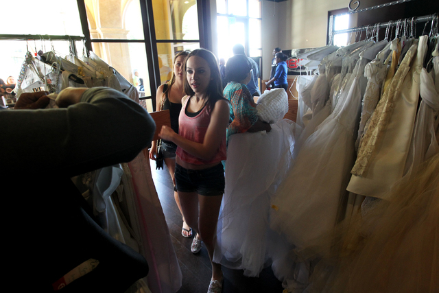 Teens enter and begin searching for a dress at the annual Gown Town event, sponsored by HELP of Southern Nevada, which provides high school students with an affordable alternative for prom dress s ...