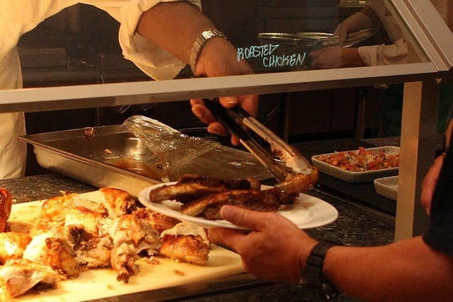 A cook places a somewhat more healthy item, a roasted chicken wing, on a plate containing, among other things, barbequed ribs, at the French Market Buffet in the Orleans hotel-casino, Thursday, Se ...