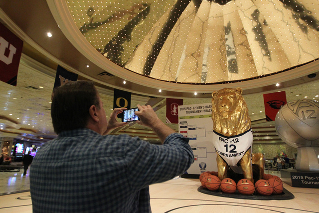 Dennis Runyan takes a photo of the Pac -12 decorated lion statue at the lobby of the MGM Grand casino-hotel in Las Vegas Wednesday, March 11, 2015. The Pac -12 tournament is scheduled from March 1 ...