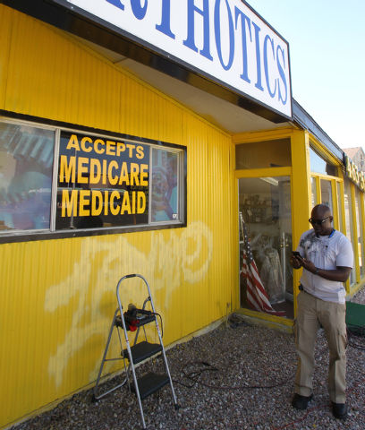 Oluwole Adegboruwa, owner of Flotsol, Inc. Medical Supplies at 2411 West Charleston Blvd. in Las Vegas, prepares Monday, March 9, 2015, to remove a sign stating that his business accepts Medicare  ...