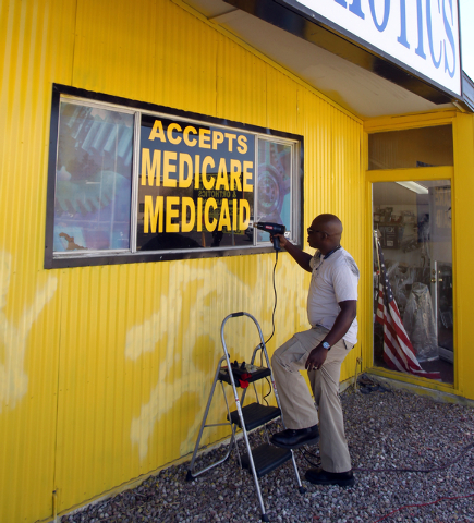 Oluwole Adegboruwa, owner of Flotsol, Inc. Medical Supplies at 2411 West Charleston Blvd. in Las Vegas, prepares Monday, March 9, 2015, uses a heat gun to remove a sign stating that his business a ...