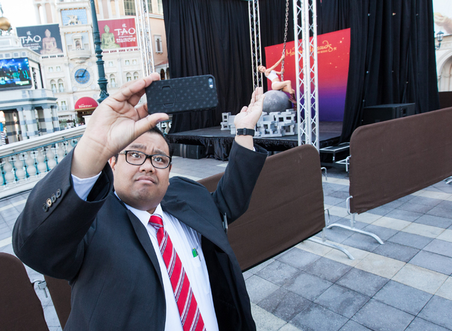 Paul Dungo, manager of engagement for the Venetian hotel-casino, takes a selfie with a wax figure of Miley Cyrus on a wrecking ball outside of the Venetian hotel-casino in Las Vegas on Monday, Mar ...