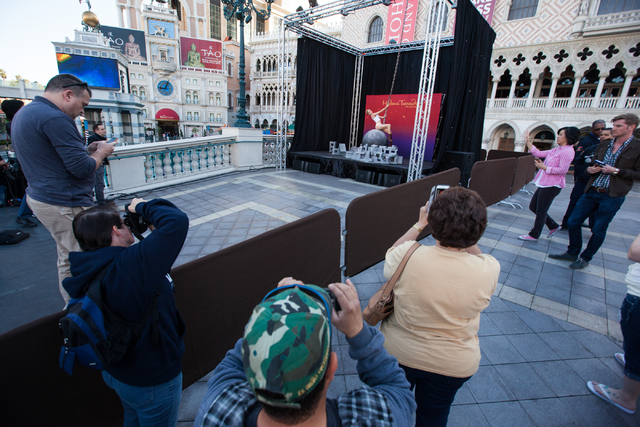People take photos as a wax figure of Miley Cyrus on top of a wrecking ball, created by Madame Tussauds' studio team, is unveiled outside of the Venetian hotel-casino in Las Vegas on Monday, March ...