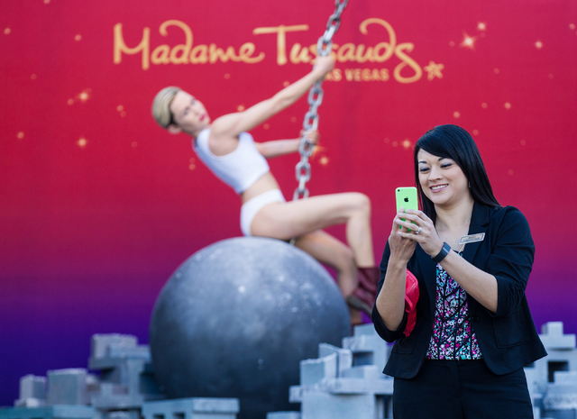 Irazu Velasquez, engagement coordinator for the Venetian hotel-casino, takes a selfie with a wax figure of Miley Cyrus on top of a wrecking ball. (Chase Stevens/Las Vegas Review-Journal)