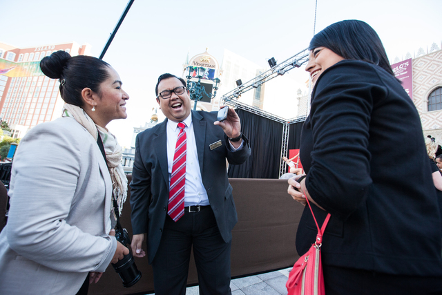 Paul Dungo, manager of engagement for the Venetian hotel-casino, center, laughs while showing a photo of himself with a wax figure of Miley Cyrus on top of a wrecking ball to coworkers Sandra Dipr ...