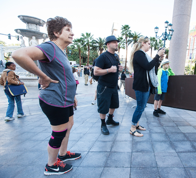 People look on at a wax figure of Miley Cyrus on top of a wrecking ball, created by Madame Tussauds' studio team, after it is unveiled outside of the Venetian hotel-casino in Las Vegas on Monday,  ...