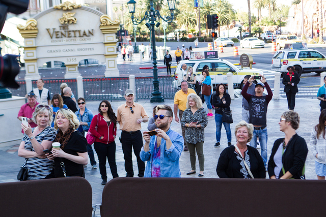 People wait for a wax figure of Miley Cyrus on top of a wrecking ball, created by Madame Tussauds' studio team, to be unveiled outside of the Venetian hotel-casino in Las Vegas on Monday, March 9, ...