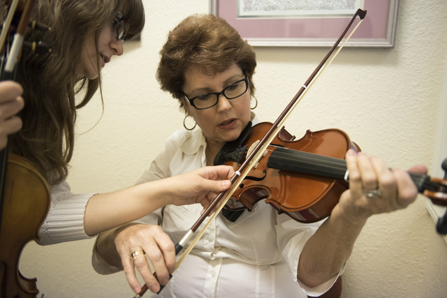 Sixty-two-year-old Martha Kilcoyne, right, is taught how to play the violin by music instructor Stacy Honaker at the Brill Music Academy in Las Vegas on Saturday, March 14, 2015. (Martin S. Fuente ...